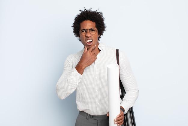 Młody czarny afro mężczyzna z szeroko otwartymi ustami i oczami i ręką na brodzie, czuje się nieprzyjemnie zszokowany, mówi co lub wow
