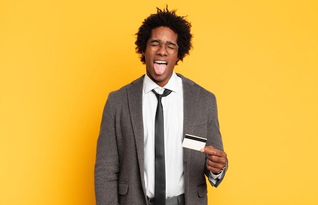Młody czarny afro mężczyzna z wesołym, beztroskim, buntowniczym nastawieniem, żartuje i wystawiający język, dobrze się bawi