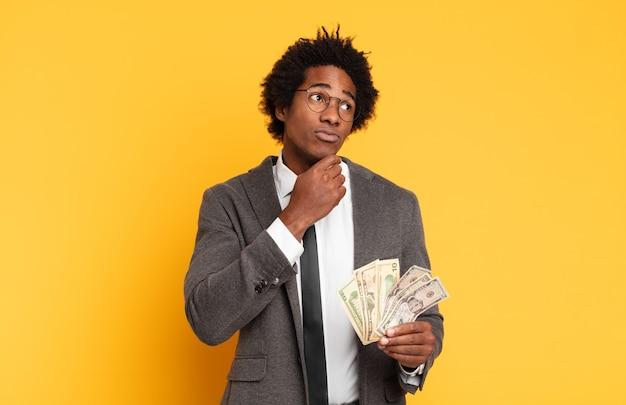 Młody czarny afro myślący, niepewny i zdezorientowany, z różnymi opcjami, zastanawiający się, jaką decyzję podjąć