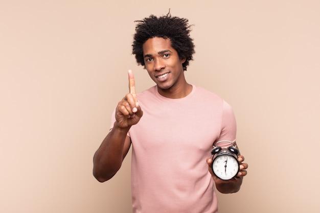 Młody czarny afro uśmiechający się dumnie i pewnie w triumfującej pozie numer jeden, czując się jak przywódca