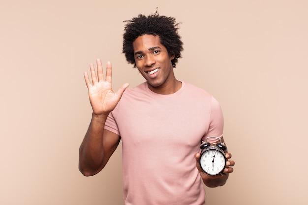 Młody czarny afro uśmiechający się radośnie i wesoło, machający ręką, witający i witający lub żegnający się