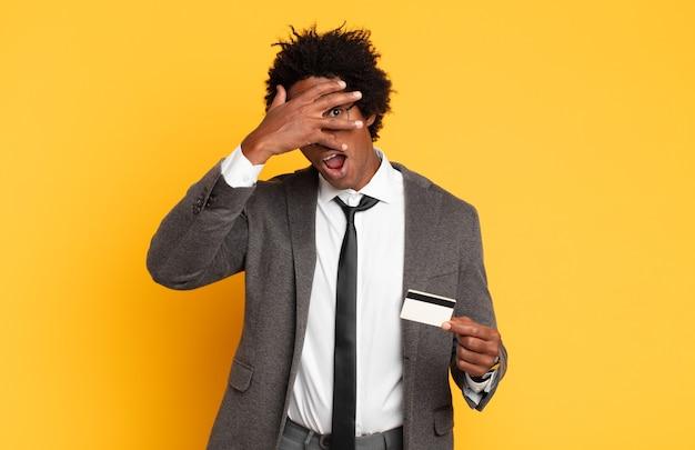 Młody czarny afro wyglądający na zszokowanego, przestraszonego lub przerażonego, zakrywający twarz dłonią i zerkający między palcami