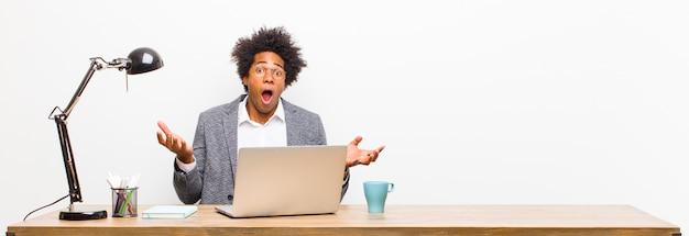 Młody czarny biznesmen czuje się bardzo zszokowany i zaskoczony, niespokojny i panikuje, z zestresowanym i przerażonym spojrzeniem na biurku