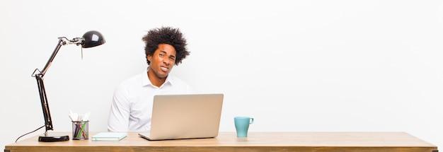 Młody czarny biznesmen czuje się smutny, zdenerwowany lub zły i patrzy w bok z negatywnym nastawieniem, marszcząc brwi w nieporozumieniu na biurku