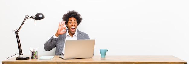 Młody czarny biznesmen czuje się udany i zadowolony, uśmiechając się z szeroko otwartymi ustami, co dobrze podpisać ręką na biurku