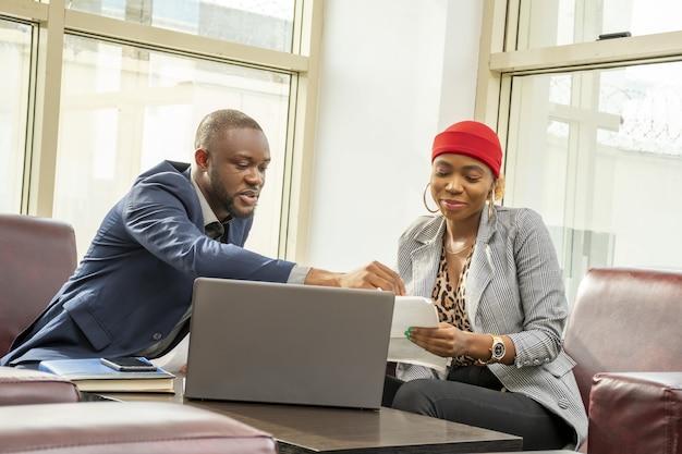Młody czarny biznesmen i kobieta przechodzą razem przez papierkową robotę