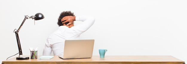Młody czarny biznesmen myśli lub wątpi, drapie się po głowie, czuje się zdziwiony i zdezorientowany, lub widok z tyłu na biurku