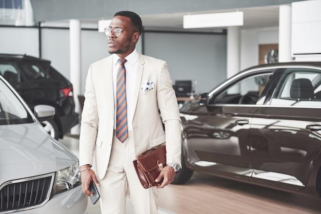 Młody czarny biznesmen na auto salonu tle. koncepcja sprzedaży i wynajmu samochodów