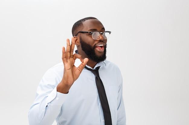 Młody czarny biznesmen o szczęśliwym spojrzeniu, uśmiechnięci, gestykulując, pokazując znak ok.