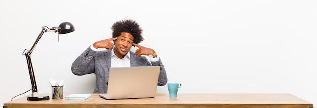 Młody czarny biznesmen, skoncentrowany i intensywnie zastanawiający się nad pomysłem, wyobrażający sobie rozwiązanie problemu lub problemu na biurku