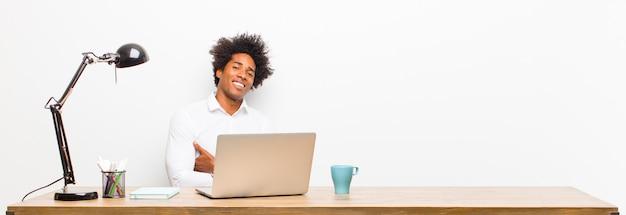Młody czarny biznesmen śmiejący się szczęśliwie ze skrzyżowanymi rękami, ze zrelaksowaną, pozytywną i zadowoloną pozą na biurku