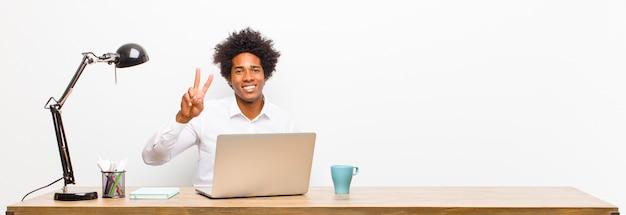 Młody czarny biznesmen uśmiecha się i szuka przyjazny, pokazując numer dwa lub drugi ręką do przodu, odliczając na biurku