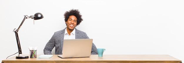 Młody czarny biznesmen uśmiecha się radośnie i swobodnie z pozytywnym, szczęśliwym, pewnym siebie i zrelaksowanym wyrazem na biurku