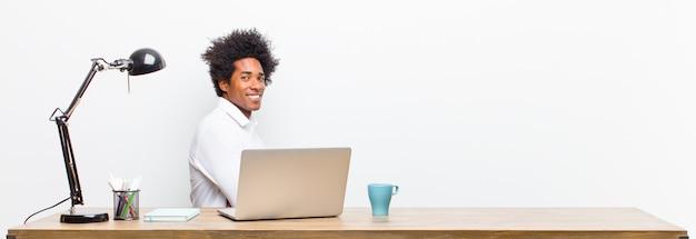 Młody czarny biznesmen uśmiecha się ze skrzyżowanymi rękami i szczęśliwy, pewny siebie, zadowolony wyraz twarzy, widok z boku na biurku