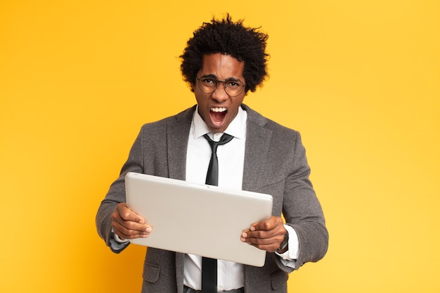 Młody czarny biznesmen z laptopem