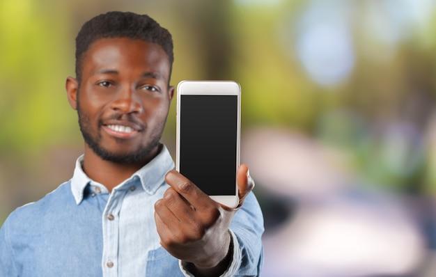 Młody czarny biznesowy mężczyzna używa jego telefon komórkowego