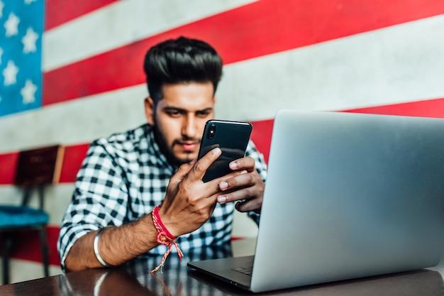 Młody, czarny brodaty biznesmen w zwykłych ubraniach używa smartfona i uśmiecha się podczas pracy z laptopem w gastropubie.