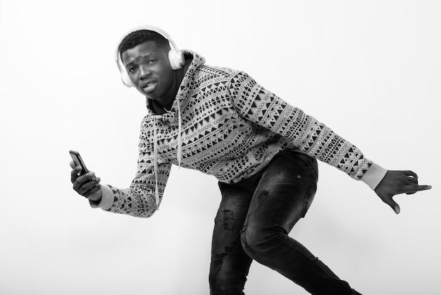 Młody czarny człowiek afryki trzymając telefon komórkowy podczas słuchania muzyki i pozowanie