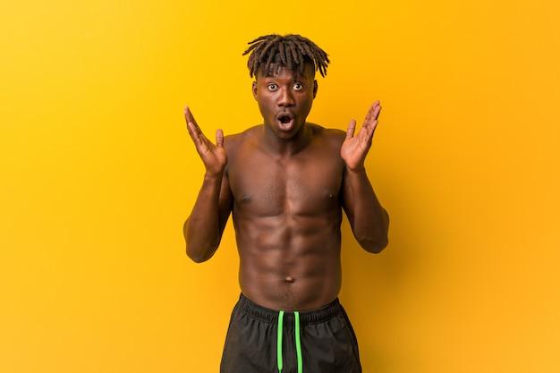 Młody czarny człowiek bez koszuli na sobie strój kąpielowy zaskoczony i zszokowany.