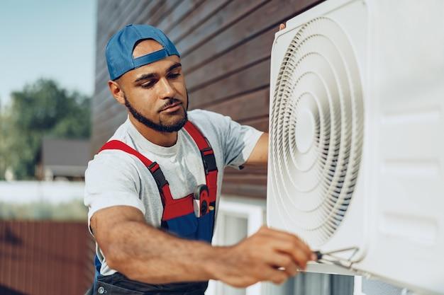 Młody czarny człowiek mechanik sprawdzanie zewnętrznego klimatyzatora