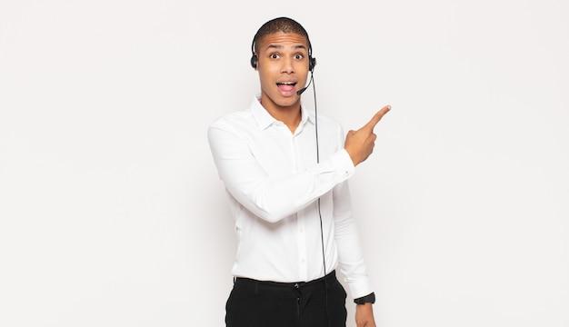 Młody czarny człowiek podekscytowany i zaskoczony, wskazując na bok i do góry, aby skopiować miejsce