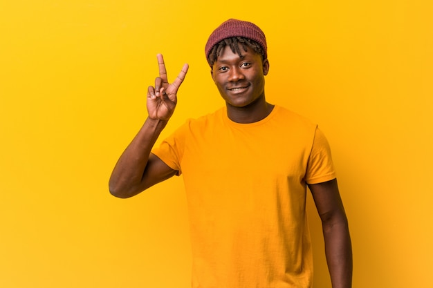 Młody czarny człowiek ubrany rastas na żółtej ścianie pokazano znak zwycięstwa i szeroko się uśmiecha.