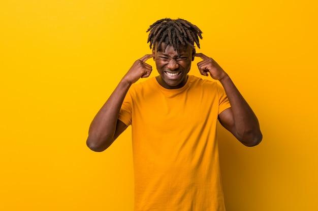 Młody czarny człowiek ubrany w rastas na żółte uszy obejmujące rękami.