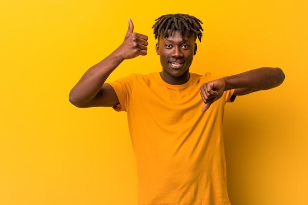 Młody czarny człowiek ubrany w rastas na żółto pokazujący kciuki do góry i kciuki w dół, trudny wybór