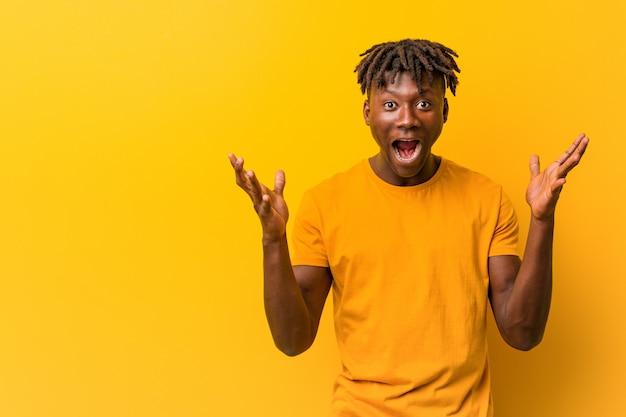Młody czarny człowiek ubrany w rastas na żółto świętuje zwycięstwo lub sukces