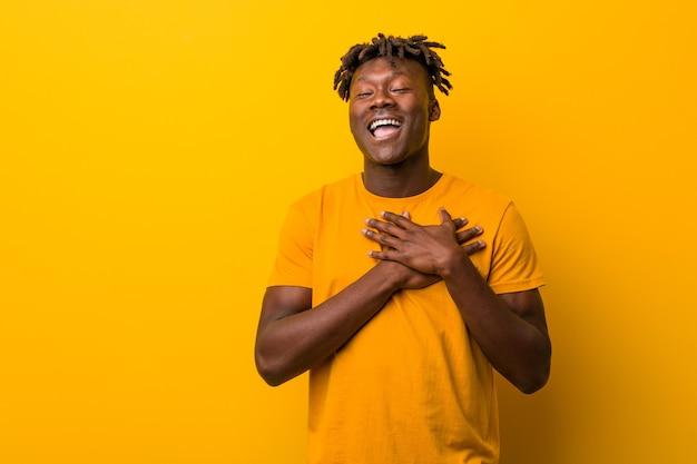 Młody czarny człowiek ubrany w rasty na żółtym, śmiejąc się, trzymając ręce na sercu, pojęcie szczęścia.