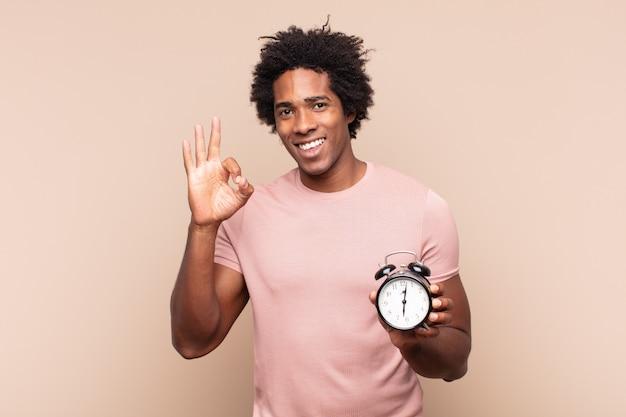Młody czarny mężczyzna afro czuje się szczęśliwy, zrelaksowany i usatysfakcjonowany, okazując aprobatę dobrym gestem, uśmiechając się