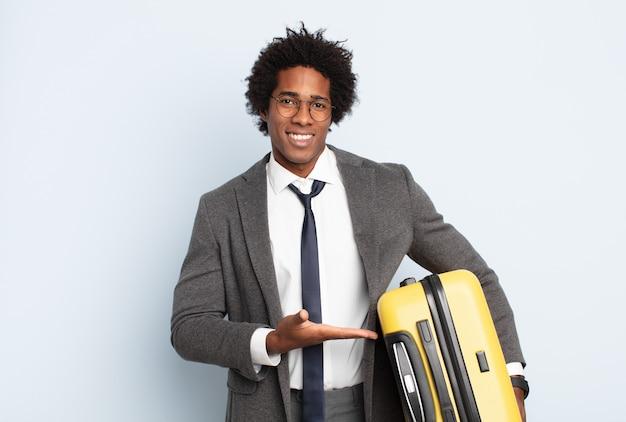 Młody czarny mężczyzna afro uśmiecha się radośnie, czuje się szczęśliwy i pokazuje koncepcję w przestrzeni kopii z dłoni