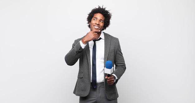 Młody czarny mężczyzna afro uśmiecha się radośnie i marzy lub wątpi, patrząc w bok