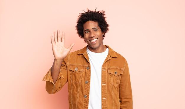 Młody czarny mężczyzna afro uśmiecha się radośnie i wesoło, macha ręką, wita i wita