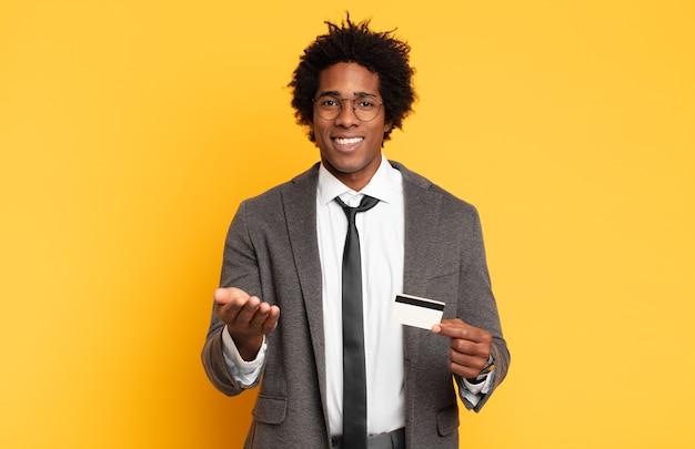 Młody czarny mężczyzna afro uśmiecha się radośnie z przyjaznym, pewnym siebie, pozytywnym spojrzeniem, oferuje i pokazuje przedmiot lub koncepcję