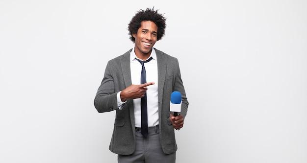 Młody czarny mężczyzna afro wygląda na podekscytowanego i zaskoczonego, wskazując na bok i w górę, aby skopiować przestrzeń