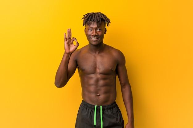 Młody czarny mężczyzna bez koszuli na sobie strój kąpielowy wesoły i pewny siebie, pokazując ok gest.