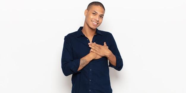 Młody czarny mężczyzna czuje się romantyczny, szczęśliwy i zakochany, uśmiechając się radośnie i trzymając się za ręce blisko serca