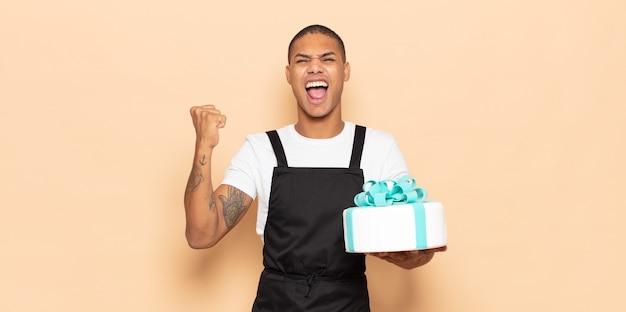 Młody czarny mężczyzna krzyczy agresywnie z gniewnym wyrazem twarzy lub z zaciśniętymi pięściami świętuje sukces