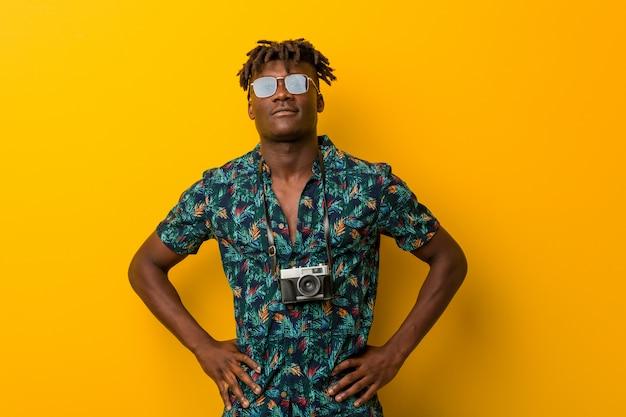 Młody czarny mężczyzna rasta na sobie wakacje wyglądają pewnie, trzymając ręce na jego biodrach.