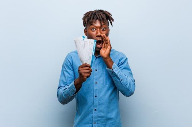 Młody czarny mężczyzna rasta trzyma bilety lotnicze krzycząc podekscytowany z przodu.