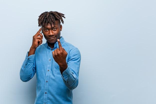 Młody czarny mężczyzna rasta trzyma telefon wskazujący na ciebie palcem, jakby zapraszając podszedł bliżej.
