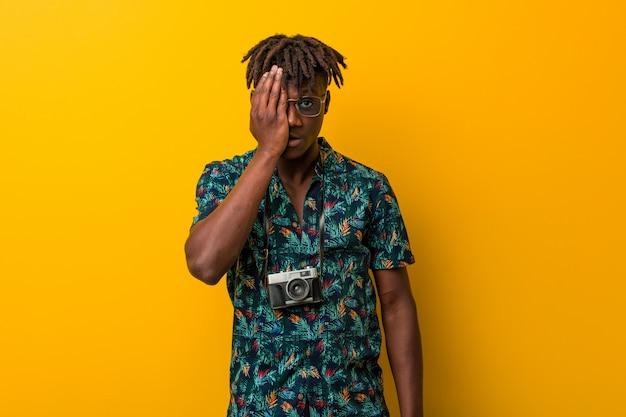 Młody czarny mężczyzna rasta ubrany w wakacyjny wygląd zabawy, obejmujący połowę twarzy dłonią.