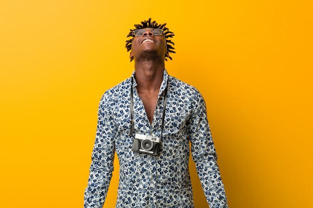 Młody czarny mężczyzna rasta w wakacyjnym wyglądzie zrelaksowany i szczęśliwy ze śmiechem, z wyciągniętą szyją pokazującą zęby.