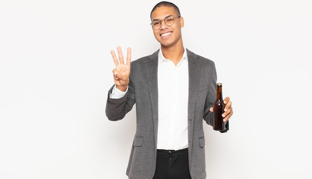Młody czarny mężczyzna uśmiechający się i wyglądający przyjaźnie, pokazujący numer trzy lub trzeci z ręką do przodu, odliczający w dół