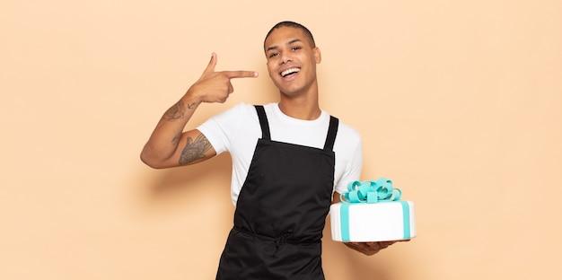 Młody czarny mężczyzna uśmiechający się pewnie, wskazując na własny szeroki uśmiech, pozytywną, zrelaksowaną, zadowoloną postawę