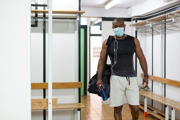 Młody czarny mężczyzna w ubrania sportowe w szatni siłowni. nosi maskę medyczną jako środek ochronny przed koronawirusem covid-19.