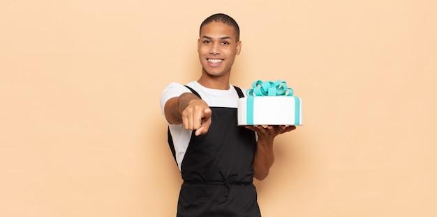 Młody czarny mężczyzna wskazujący na aparat z zadowolonym, pewnym siebie, przyjaznym uśmiechem, wybierający ciebie