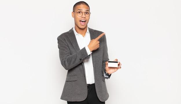 Młody czarny mężczyzna wygląda podekscytowany i zaskoczony, wskazując na bok i do góry, aby skopiować miejsce