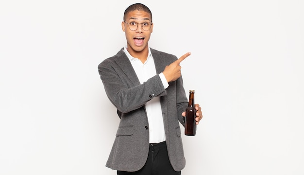 Młody czarny mężczyzna wyglądający na podekscytowanego i zaskoczonego, wskazujący na bok i w górę, aby skopiować przestrzeń